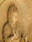 Kuan Yin image of buddha , Wood carving in a thai temple. — Stock Photo
