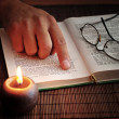 An open old book by the candlelight, - Stock Photo