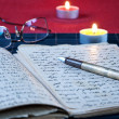 An open old book by the candlelight, — Foto Stock