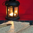 Stock Photo: An open old book by the candlelight
