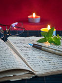 An open old book by the candlelight — Стоковое фото