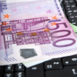 Laptop keyboard with 500 euro bill — Stock Photo