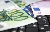 Clavier d'ordinateur portable noir avec des factures de 100 euro — Photo