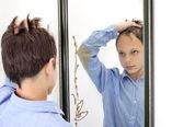 Ung pojke kamning hans hår i spegeln — Stockfoto