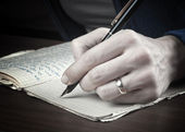 Woman hand writes on a paper — Stock Photo