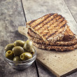 Toasted bread and olives — Stock Photo