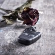 Dried rose and car keys on the table — Stock Photo