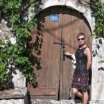 Woman in front of old wooden door — Stock Photo