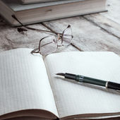 Old book with glasses lay on a table — Foto Stock