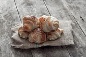 Croissant over wooden background — Stock Photo