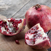 Broken pomegranate on wooden surface — Stock Photo