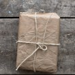 Package wrapped in wrinkled brown paper lying on weathered wood — Stock Photo #51191435