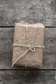 Package wrapped in wrinkled brown paper lying on weathered wood — Stock Photo
