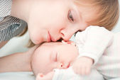 Young mother kissing her slipping newborn baby — Stock Photo
