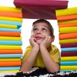 Young boy  between two piles of books — Stock Photo