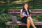 Business woman in the park working on laptop — Stock Photo