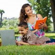 Mother reading a  book in park — Stock Photo