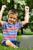 Boy using his laptop outdoor in park on grass — Stockfoto