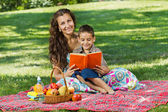 Mother and little boy in park reading book together — Foto de Stock