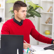 Successful businessman in red sweater in office — Stockfoto