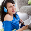 Stock Photo: Young smiling womwith tablet and headphones at home