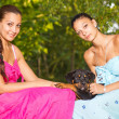Stock Photo: Two beautiful sisters with puppy in park