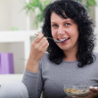 Young beautiful woman relaxing at home,eating cereals — Stock Photo