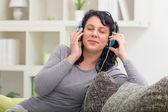 Beautiful smiling woman listening music — Стоковое фото