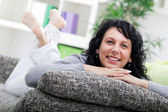 Young woman relaxed lying on couch at home — Stock Photo