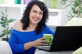 Güzel bir genç kadın içme kahve, onun evinde oturan gülümsüyor — Stok fotoğraf