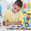 Young boy sitting at his desk at home and learn — Stockfoto