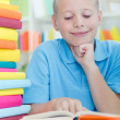 Young boy learns from books — Stok fotoğraf