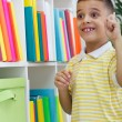 Stock Photo: Cheerful boy student has idein library