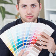 Stock Photo: Young successful businessmshowing color palettes
