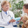 Doctor examines, young boy wearing a blue cast — Stock Photo #30556517