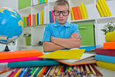 Angry and tired schoolboy studying with a pile of books on her d — Stock Photo