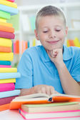 Young boy learns from books — Stock Photo
