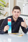 Successful businessman showing color palettes — Stock Photo
