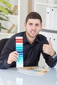 Successful businessman showing color palettes — Stock Photo