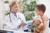 Doctor examines, young boy wearing a blue cast — Stock Photo