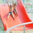 Stock Photo: Child on water slide at aquapark