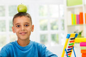 Child study and have apple in head — Stock Photo