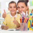 Smiling mother helping son to do his homework — Stock Photo