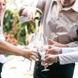Young business people pouring champagne in the glass — Stock Photo