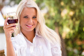 Young happy woman with glass of redwine — Stock Photo