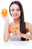 Young woman holding orange and orange juice — Stock Photo
