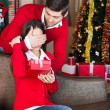 Man surprising  with a gift woman on christmas Eve — Foto de Stock