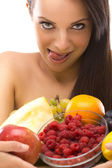 Sexy young woman holding a plate of fruit — Stock Photo