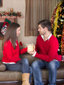 Man gives a girl a gift on Christmas Eve — Stock Photo