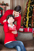 Man surprising with a gift woman on christmas Eve — Stock Photo